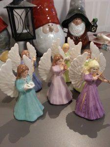 Gjutna änglar i lergods och sedan målade som porslin. I bakgrunden handmålade porslinstomtsr.